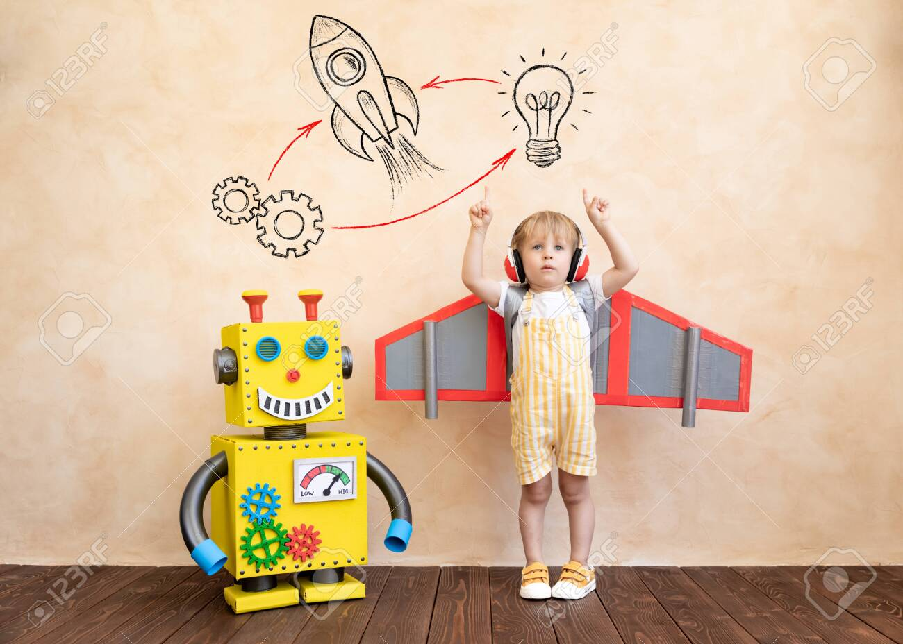 Happy child with cardboard wings. Funny kid playing with toy handmade robot. Success, creative and innovation technology concept - 143751380