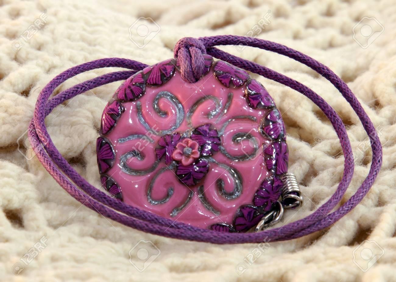 Argile Rouge A La Main Et Fleur Violette Sur Un Fond Tricote Banque