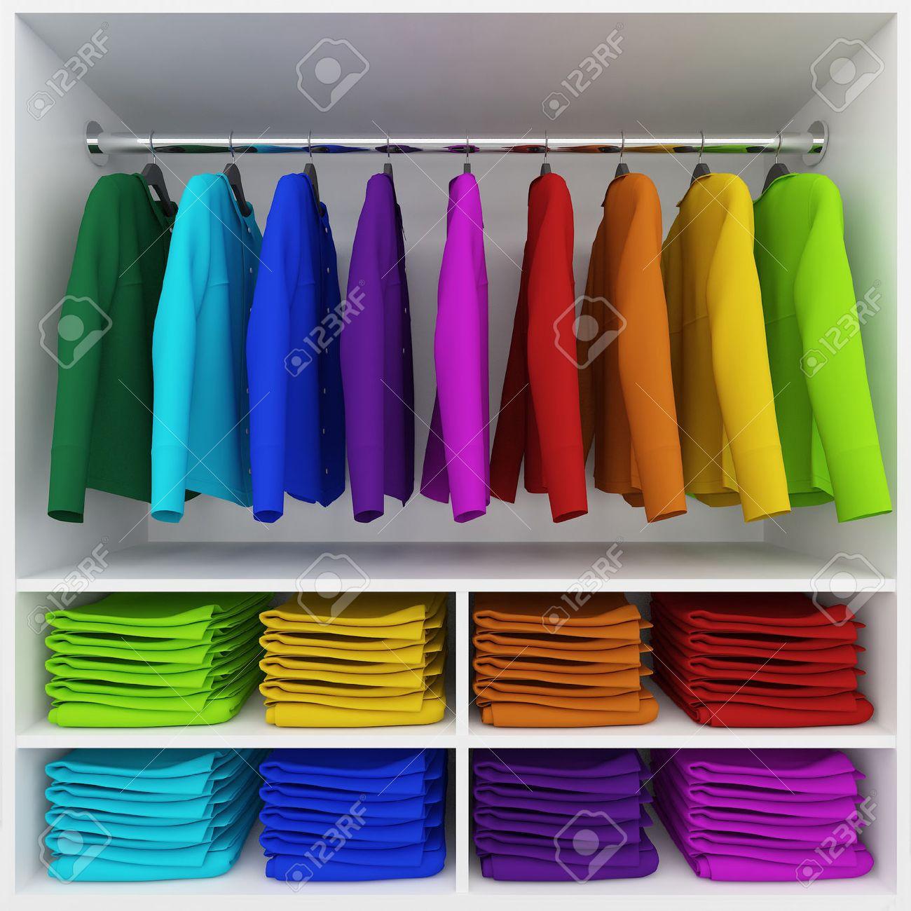 Vestiti colorati appesi e pila di vestiti armadio Archivio Fotografico - 36894419