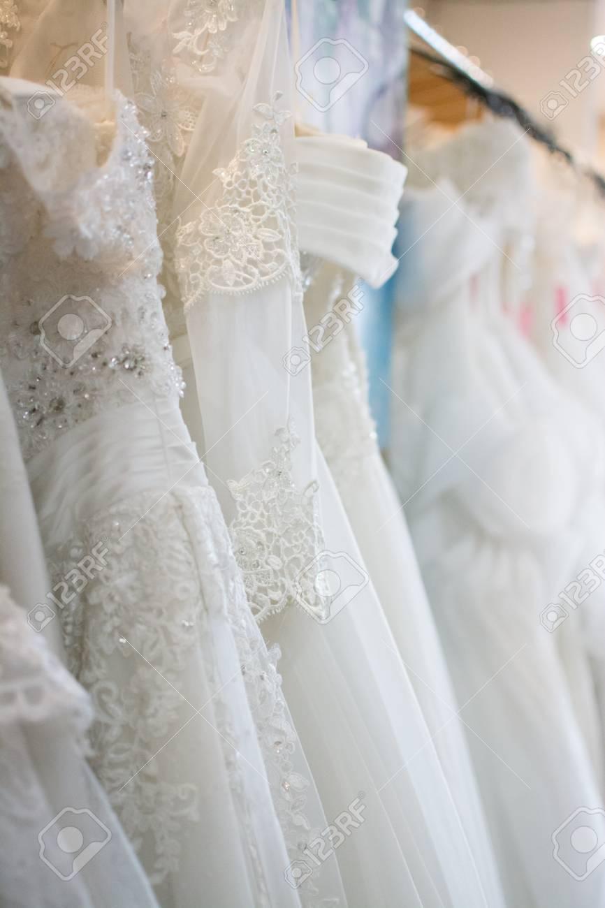 217f1a7799972 Stock Photo - white wedding dresses hanging on racks