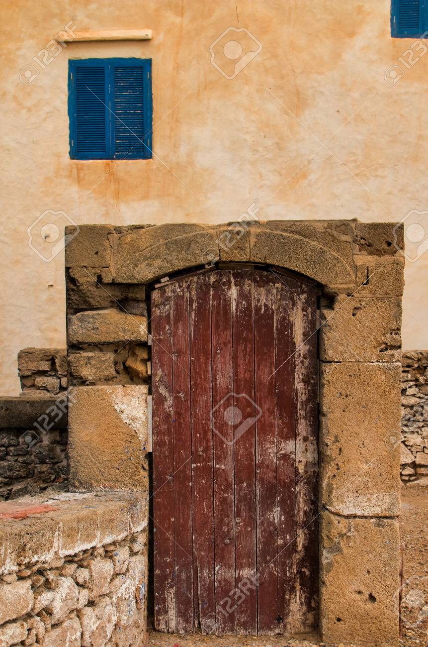 Old Wooden Gate In A Stone Frame Orange Facade And Windows With