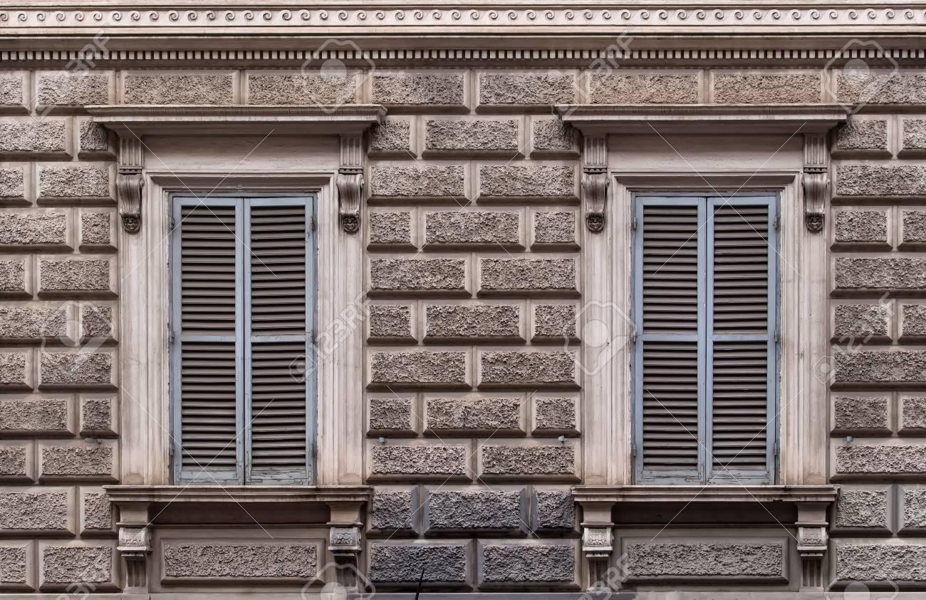 Fachada Del Edificio Decorado Con Un Diseño De Grandes Ladrillos De Piedra.  Dos Ventanas Con