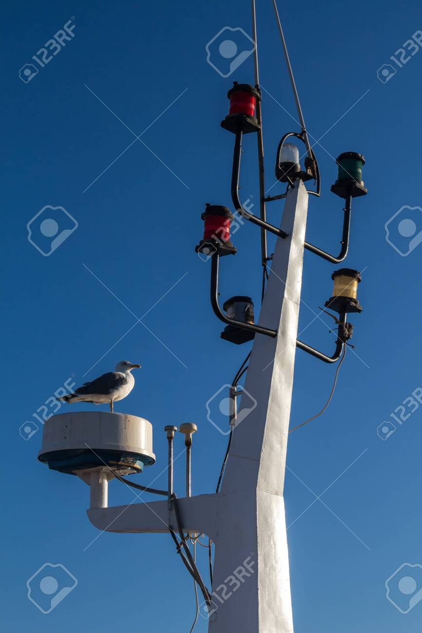 Detail of the mainmast with various colorful lights for signalization. Seagull standing. Bright clear blue sky. Essaouira, Morocco. - 140371506
