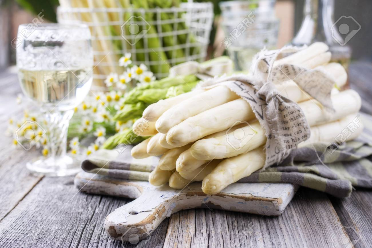 Row of green and white asparagus as close-up on a cutting board - 78669790