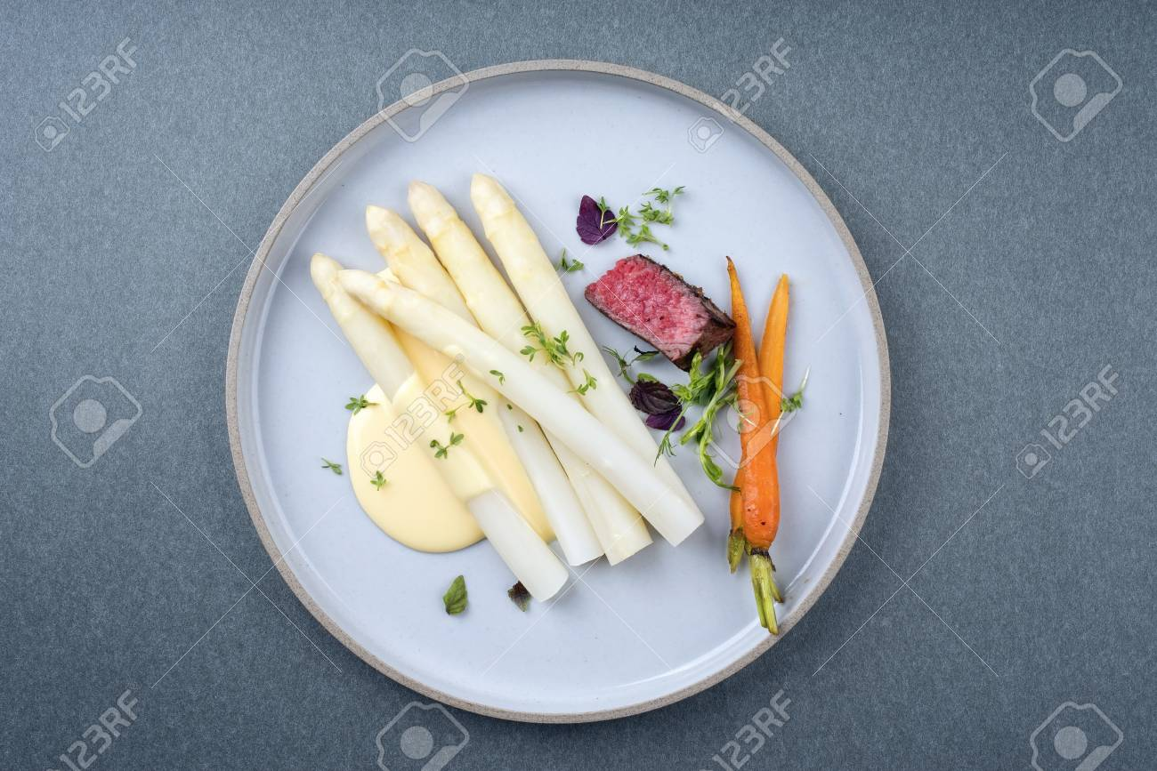 Modern barbecue dry aged sliced fillet steak with white asparagus and sauce hollandaise as closeup on a plate with copy space - 110761748