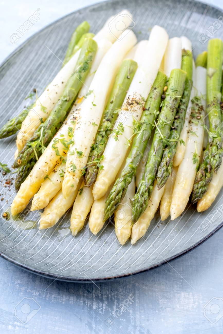 Traditional boiled white and green asparagus with butter sauce decorated with cress as closeup on a design plate on a table - 121965842