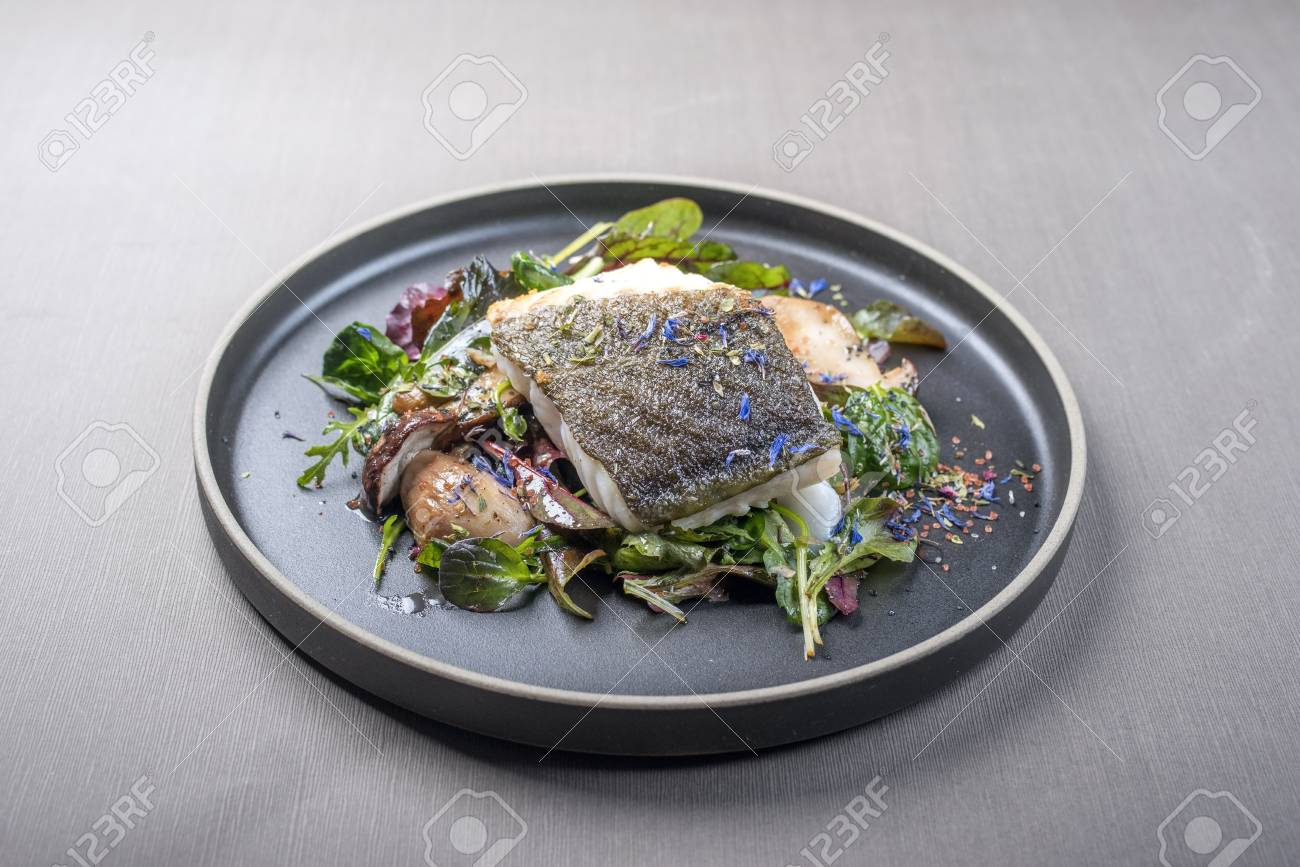 Fried Danish skrei cod fish filet with porcini mushroom and lettuce as closeup on a modern design plate with copy space - 122124968