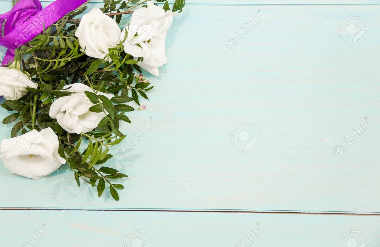 Flowers layout on white rustic background  a bouquet of roses