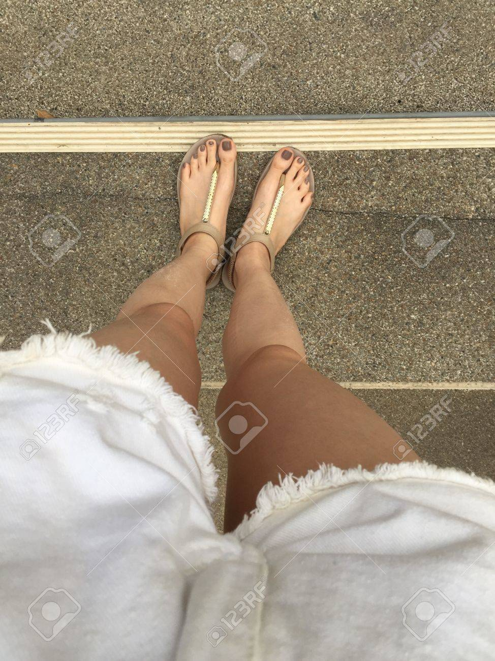 young girl feet with brown nails in gold sandals on staircase