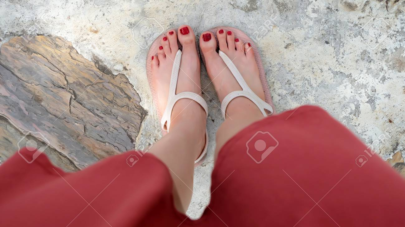 Feet Wearing Sandals And Red Nail