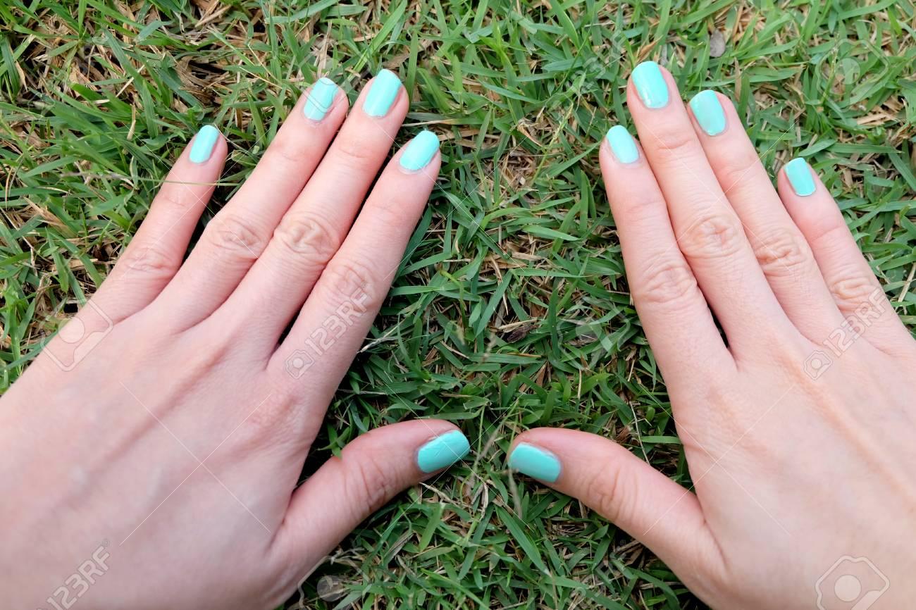 Uñas De Manicura Verde. Woman\'s Hand Nails Polish En El Green Grass ...
