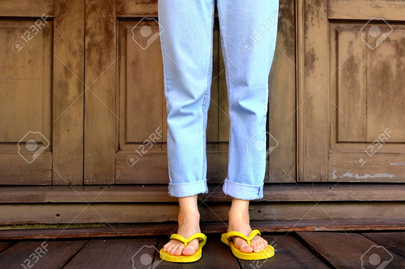 822d21d2b7d8 Stock Photo - Yellow Flip Flops. Woman Legs and Feet Wearing Yellow Sandals  Standing on Wooden Floor and wooden Wall Background Great for Any Use.
