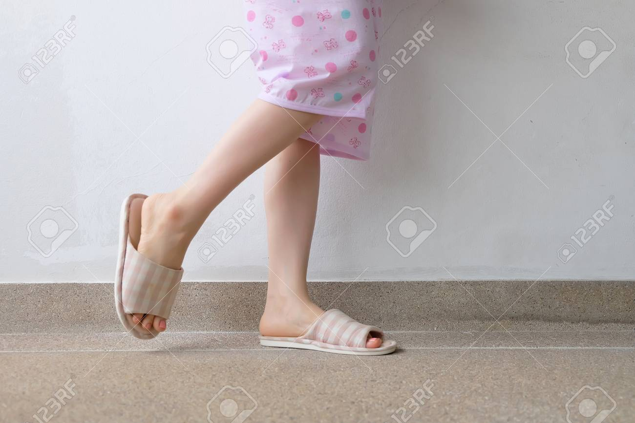 Checkered Warm Slipper With Pink Manicure Nails Female Legs And
