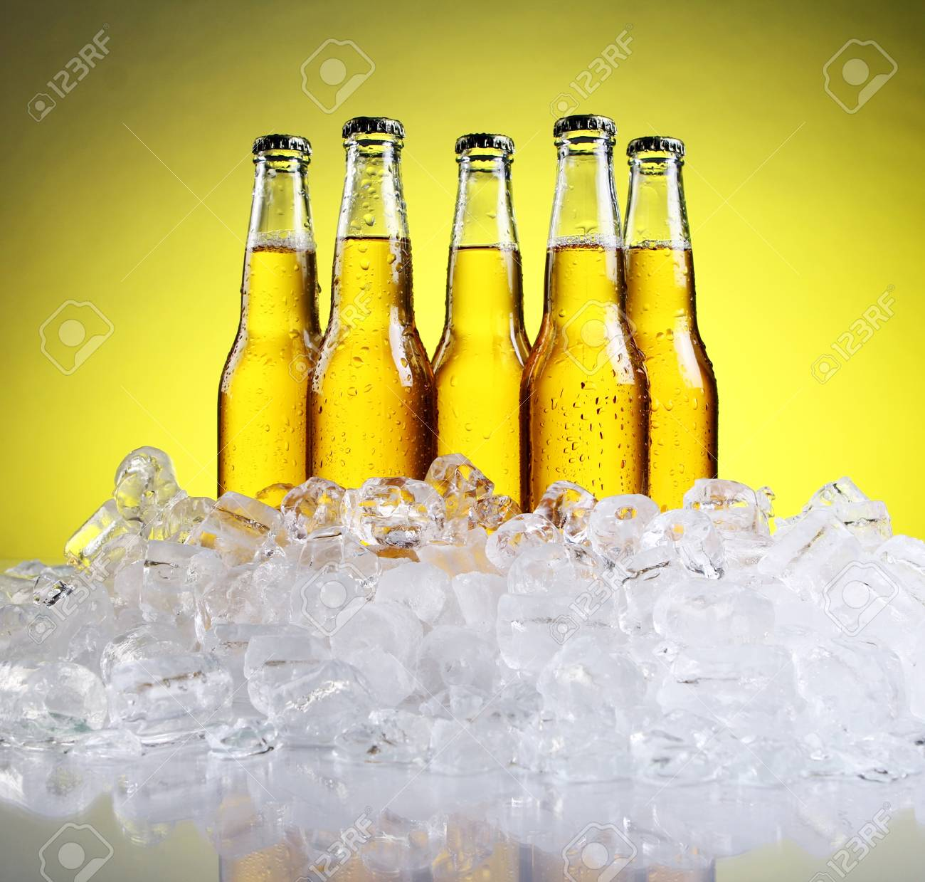 Bottles and Glass of beer with foam over yellow background Stock Photo - 9636289