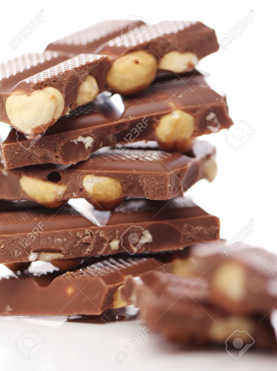 Pieces Of Milk Chocolate With Nuts Against White Background Stock ...