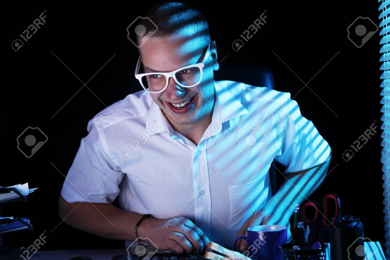 Funny nerd in glasses surfs internet at night time Stock Photo - 11929803