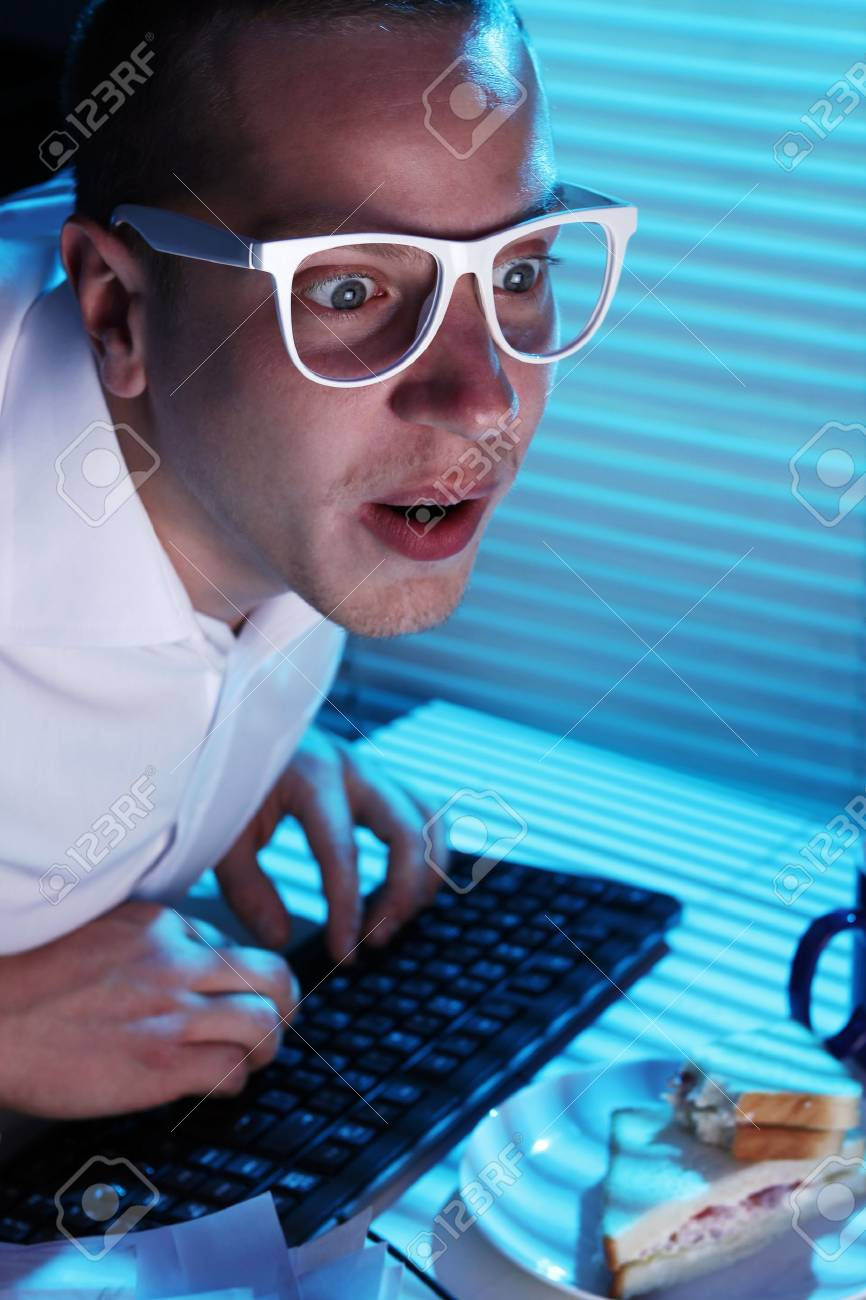 Funny nerd in glasses surfs internet at night time Stock Photo - 11929789