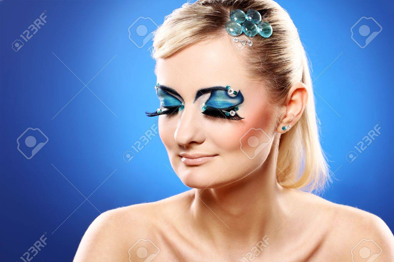 Beautiful blonde with artistic makeup over blue background Stock Photo - 12189499
