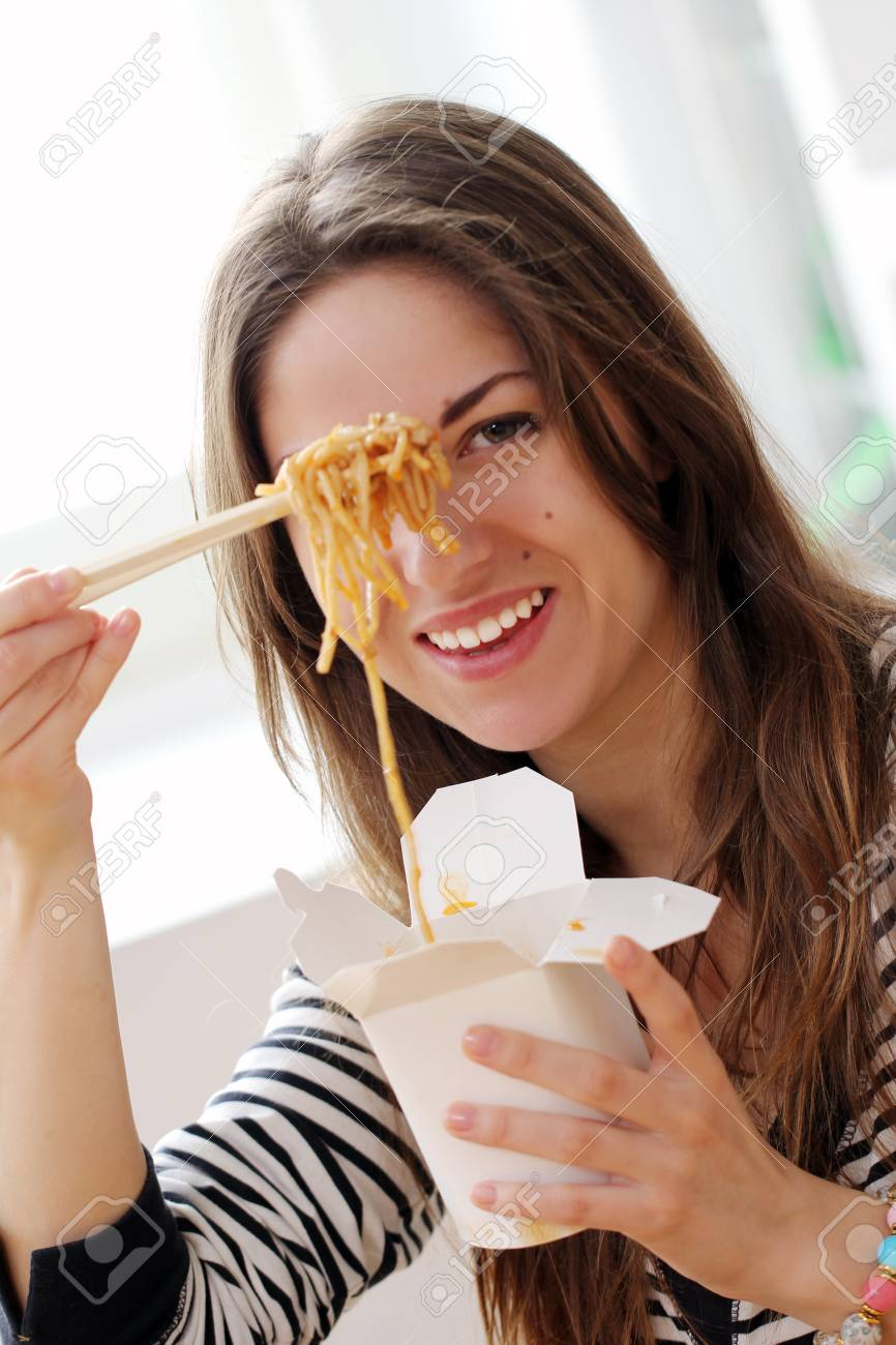 Happy woman eating noodles at home Stock Photo - 12931306