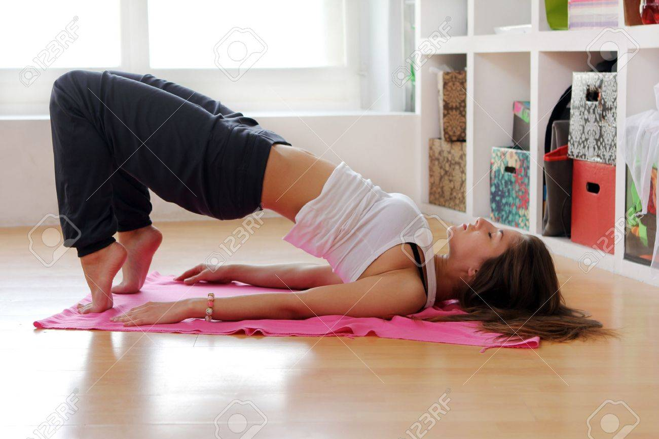 Young woman doing gymnastic exercises at home Stock Photo - 12931294