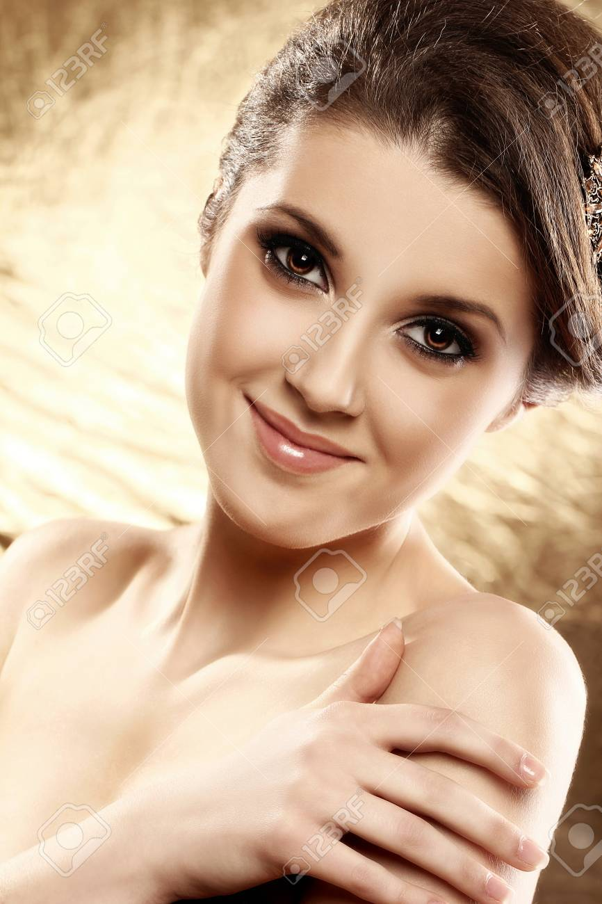 Beautiful woman with brooch in hair over golden background Stock Photo - 12933164