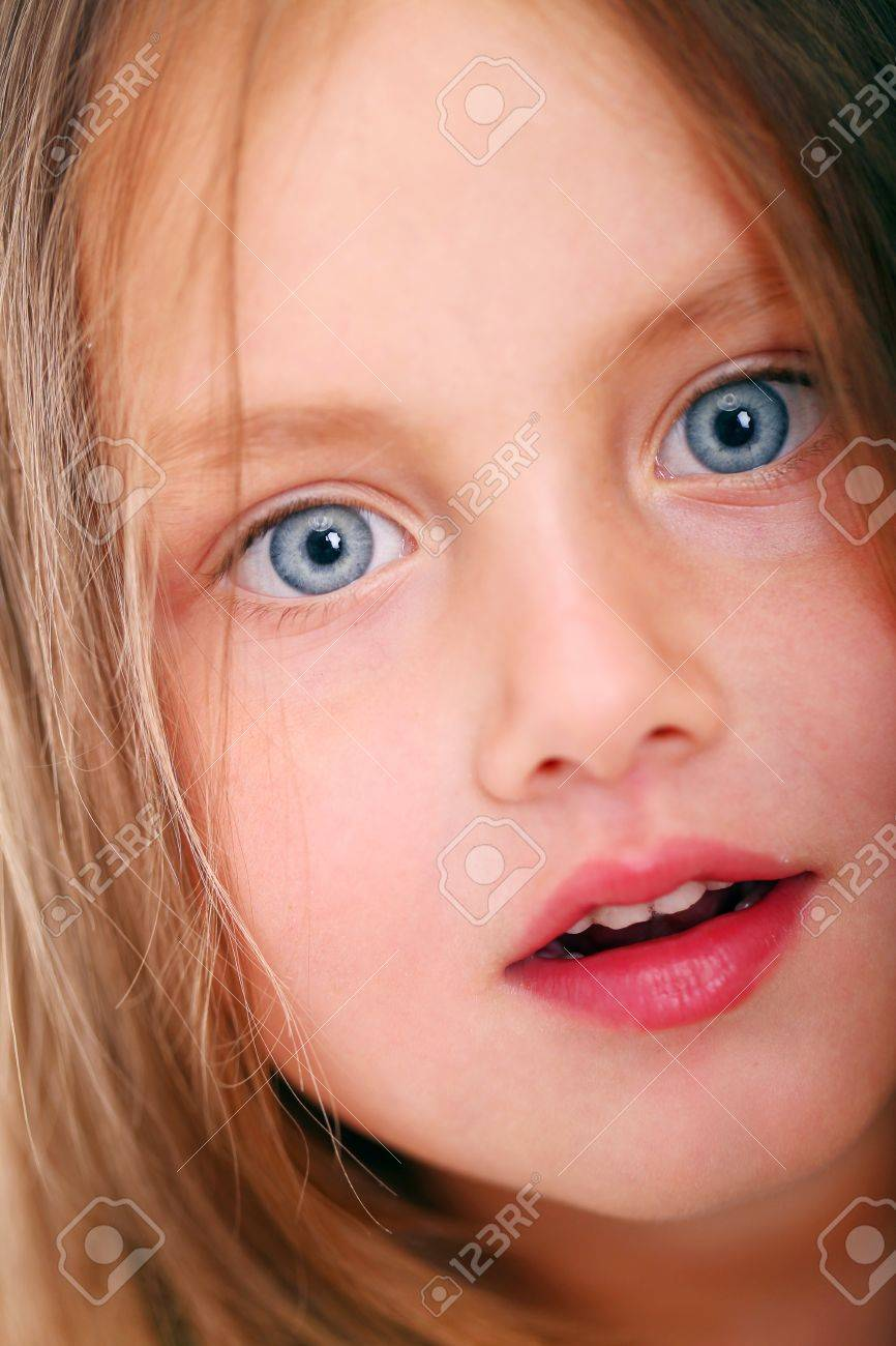 close up of little girl with big eyes looking at you stock photo