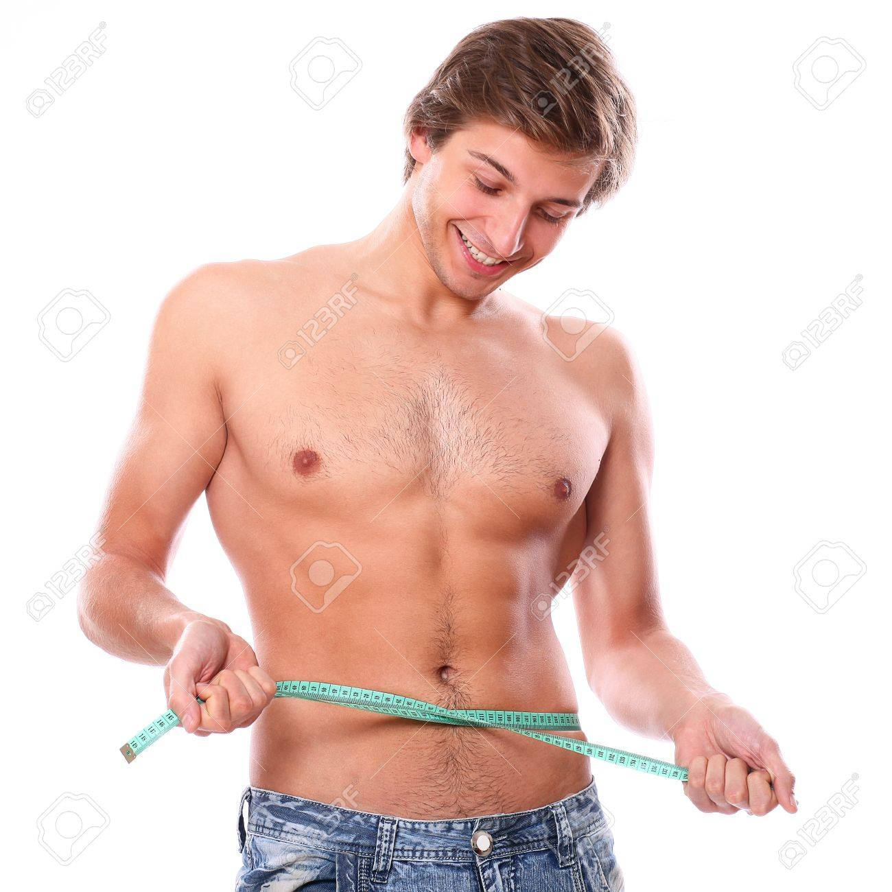 Sexy and handsome man measuring his belly after weight lose over a white background Stock Photo - 16924611