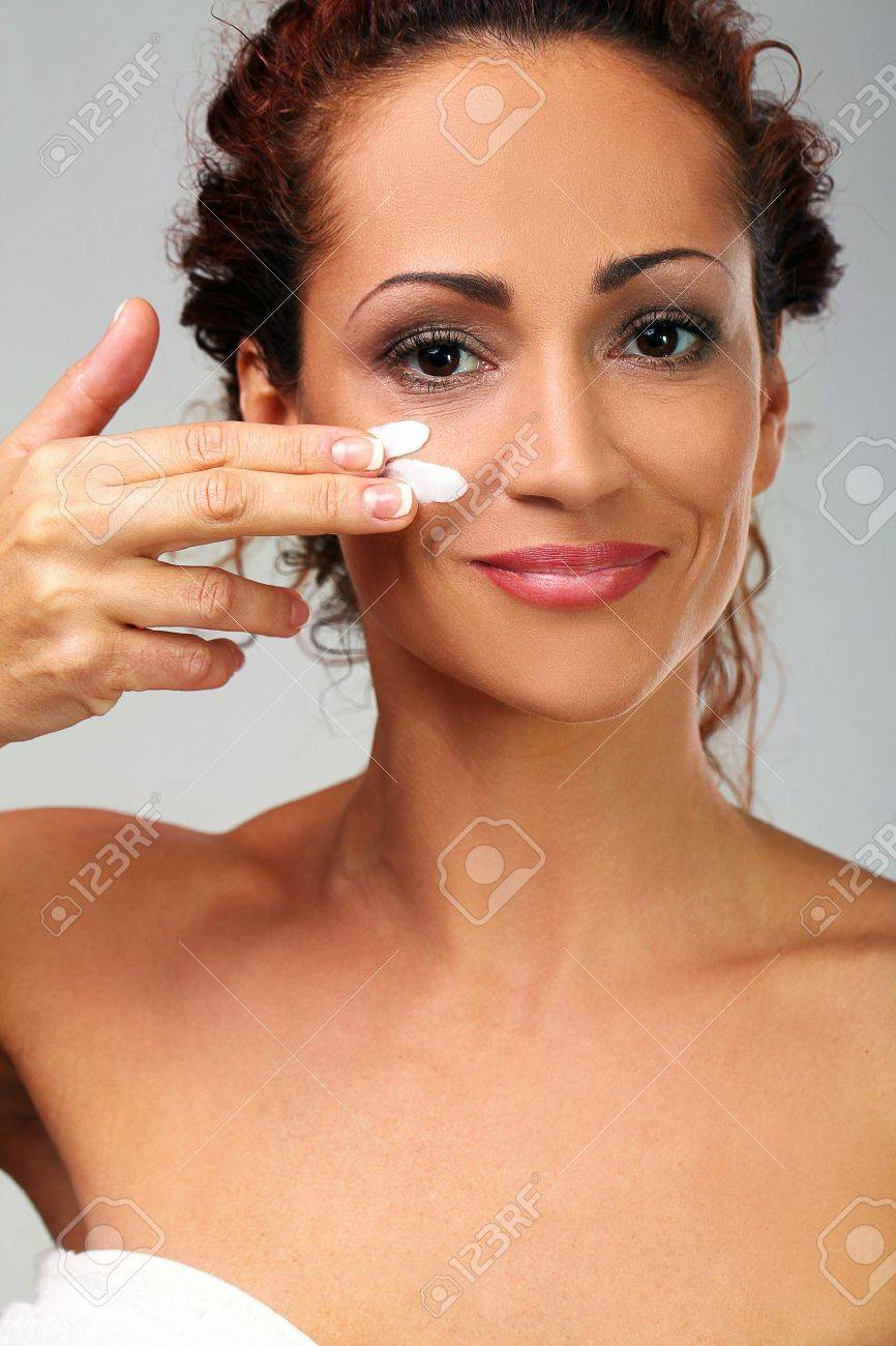 Beautiful natural middle aged woman cover face with cream isolated on grey background Stock Photo - 17488957