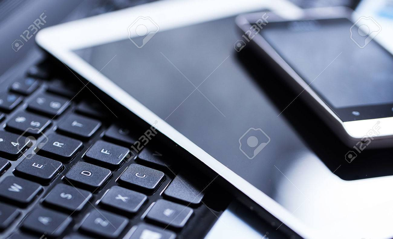 Closeup picture of a keyboard with a phone and tablet lying above it Stock Photo - 32125450