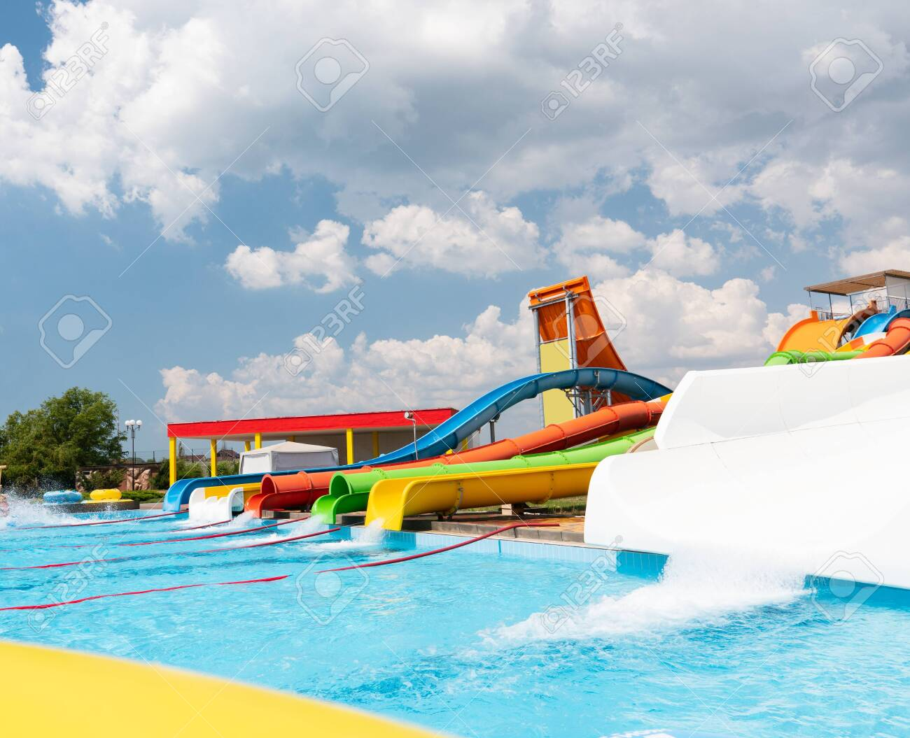 Outdoor water park. Multi-colored slides and pools. No people. - 136324643