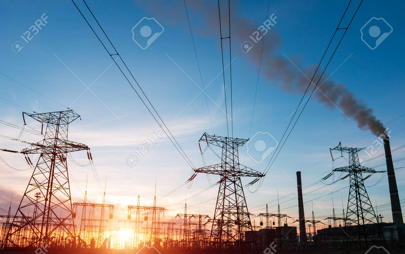 High voltage power lines at sunset. Thermal power plant. High-voltage transformer substation. - 158124092