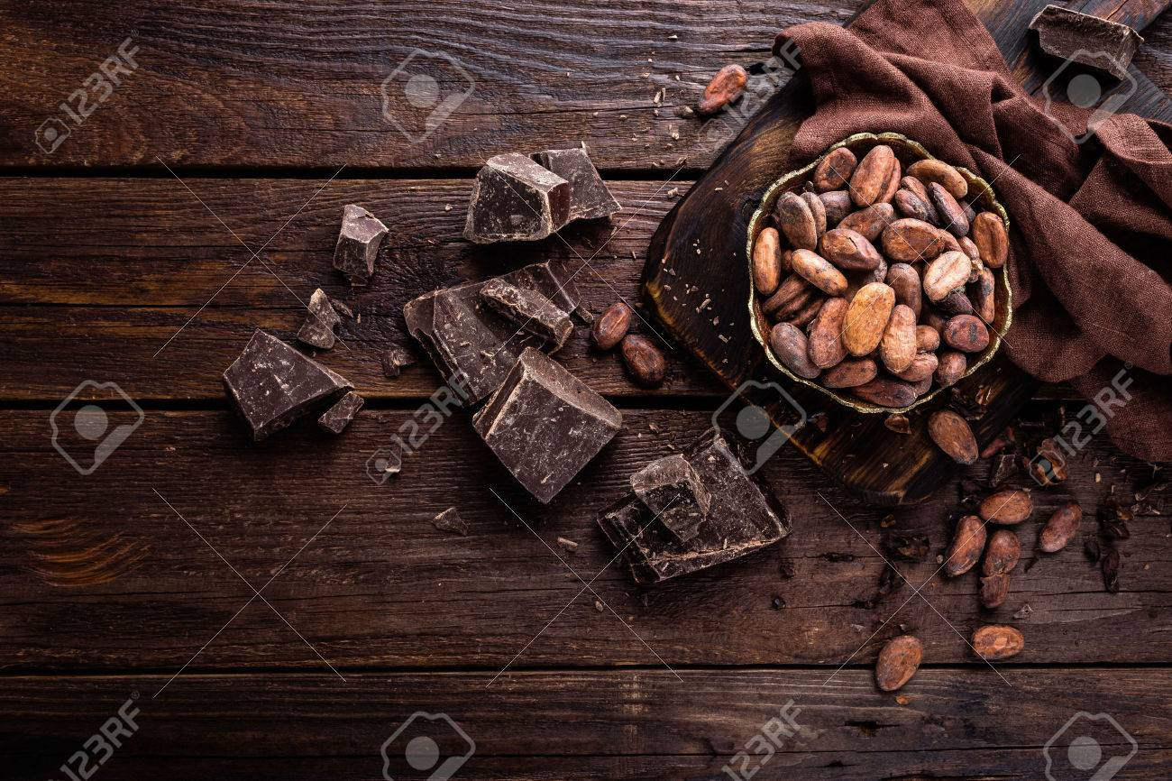 Cocoa beans and chocolate on wooden background - 73354989