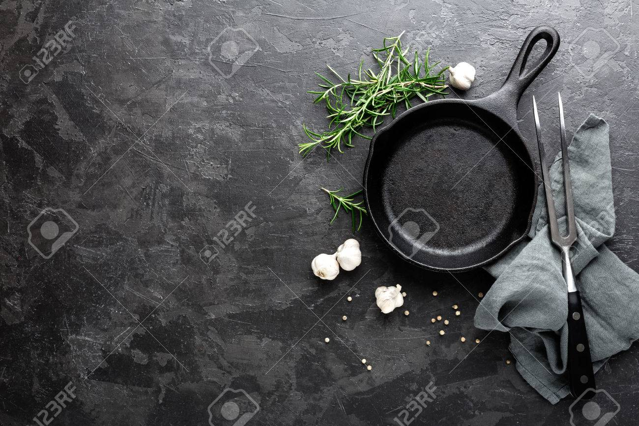 Empty cast iron frying pan on dark grey culinary background, view from above - 80047619