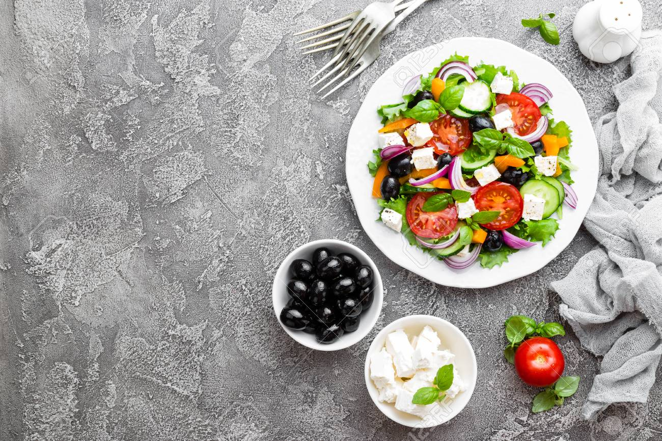 Greek salad. Fresh vegetable salad with tomato, onion, cucumbers, basil, pepper, olives, lettuce and feta cheese. Greek salad on plate - 102569495