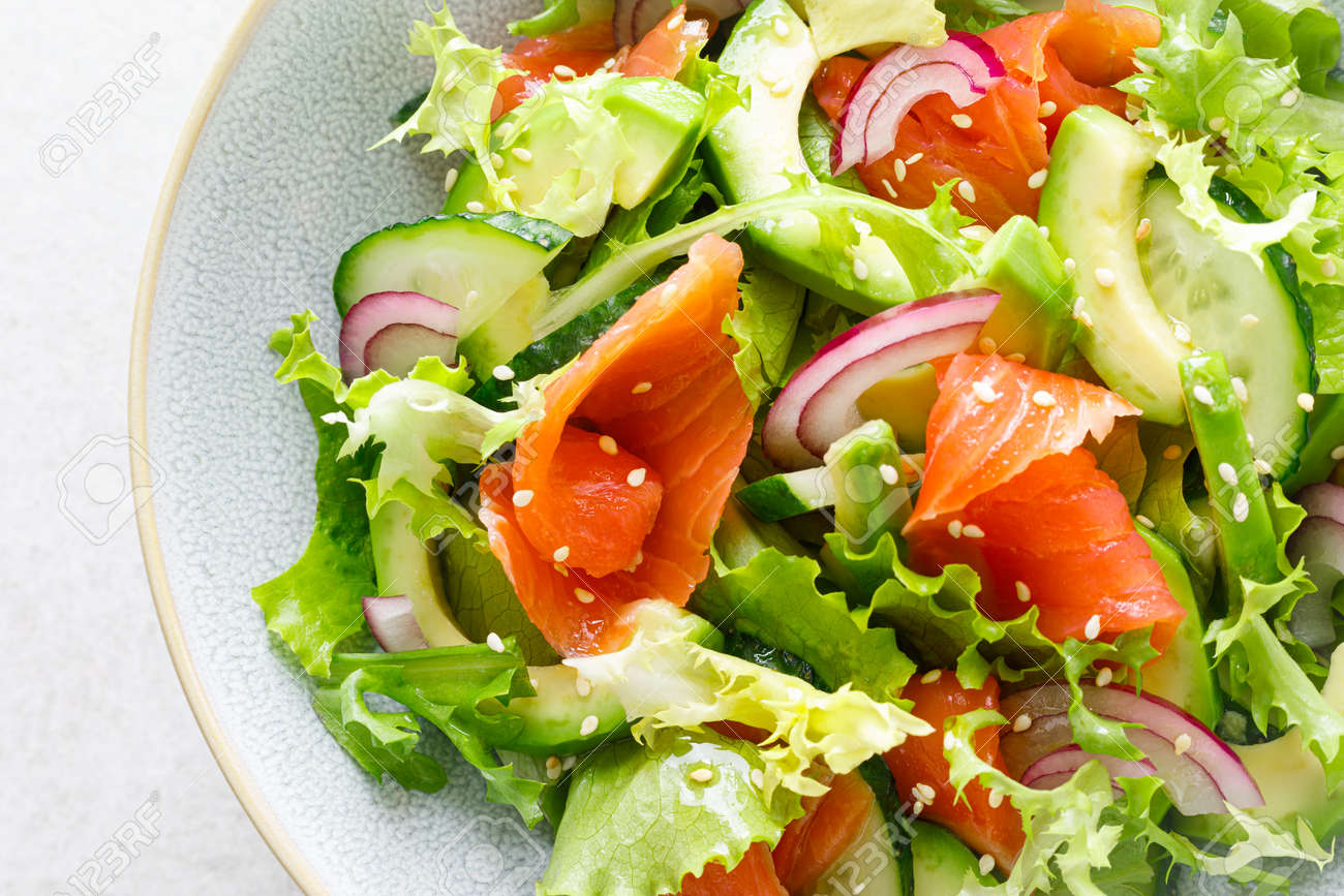 Salmon avocado salad with salted fish, lettuce, red onion and cucumbers - 158849156