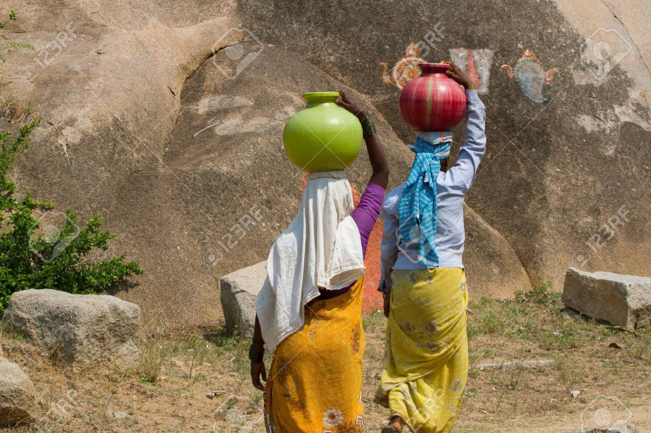 Two Indian Women Carry Water On Their Heads In Traditional Pots ...