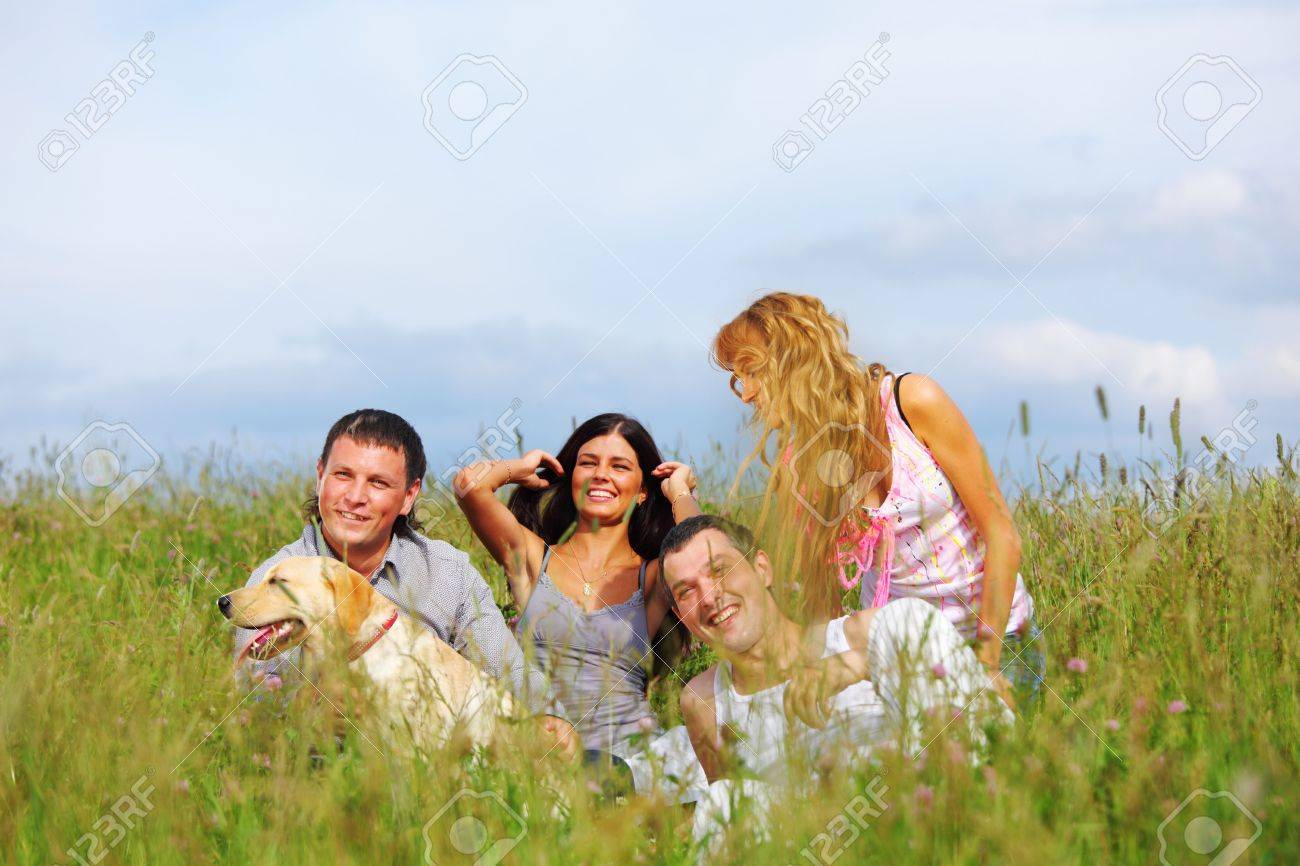 friends and dog in green grass field Stock Photo - 6318177