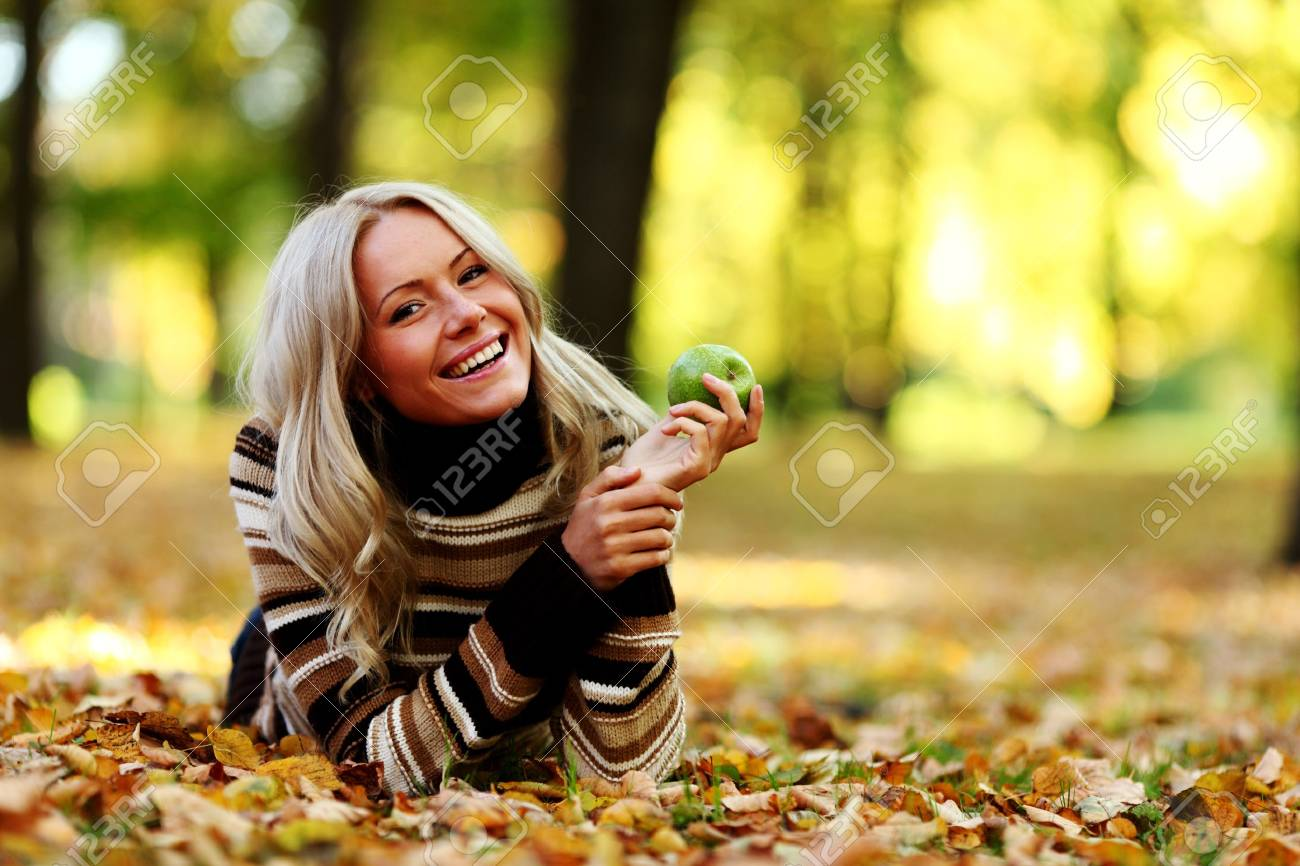 woman with green apple in autumn park Stock Photo - 8587553