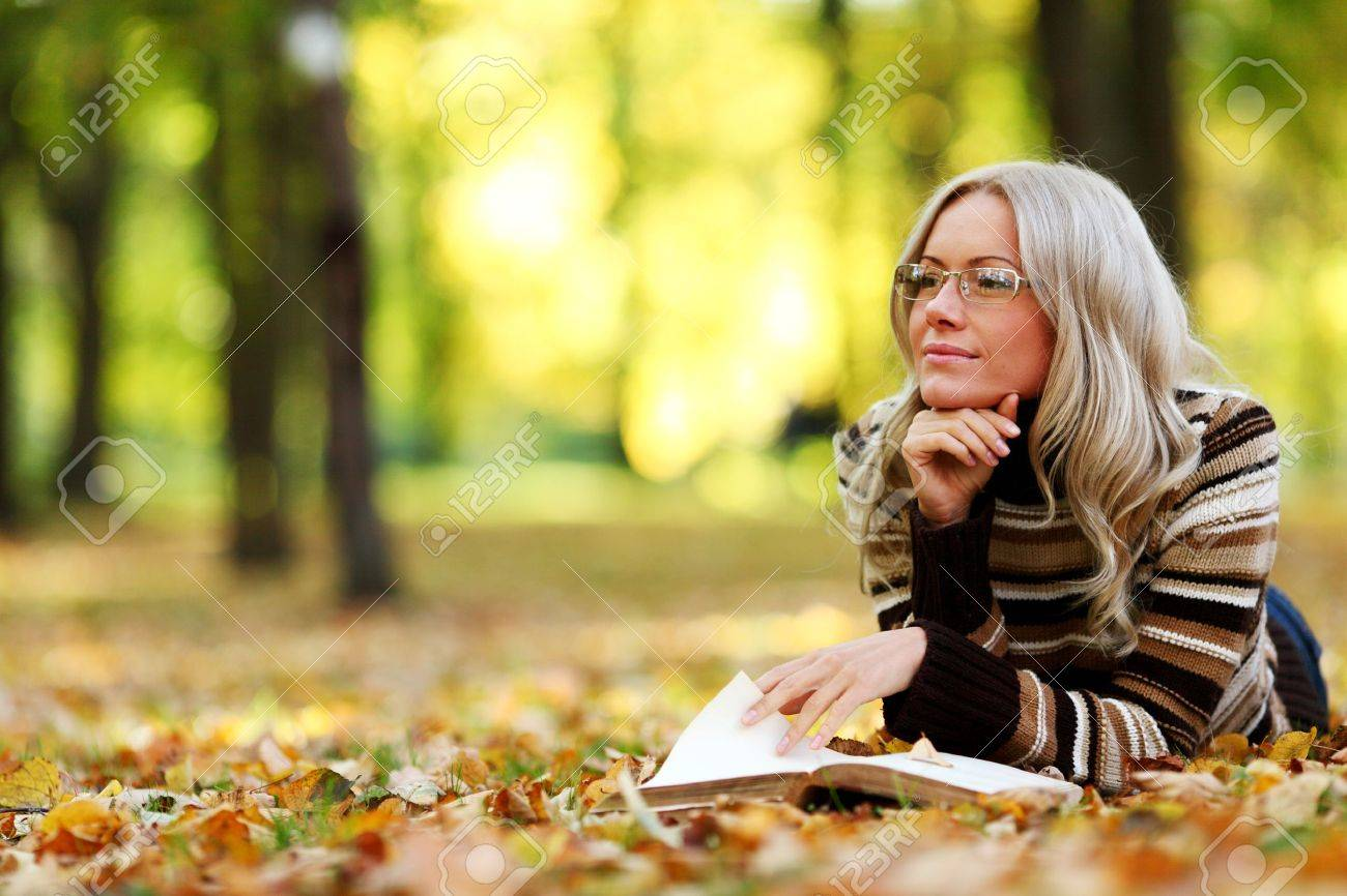 woman read the book in autumn park - 8585377