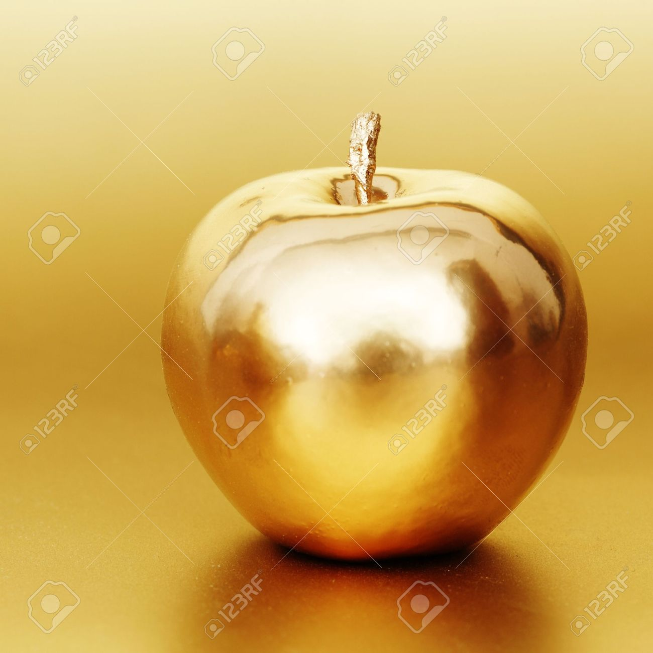 gold apple on gold background Stock Photo - 8743998