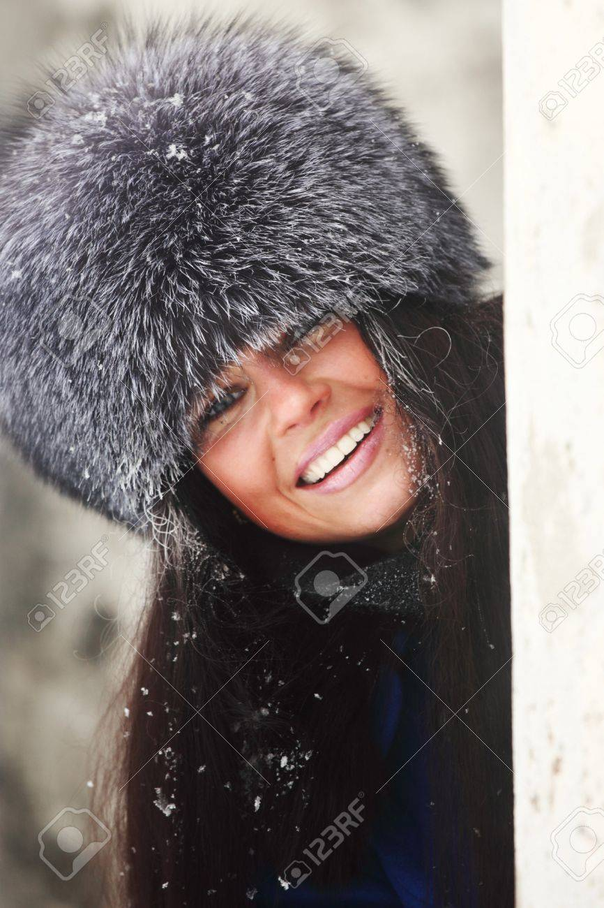 woman in fur hat hide behind column Stock Photo - 8751176