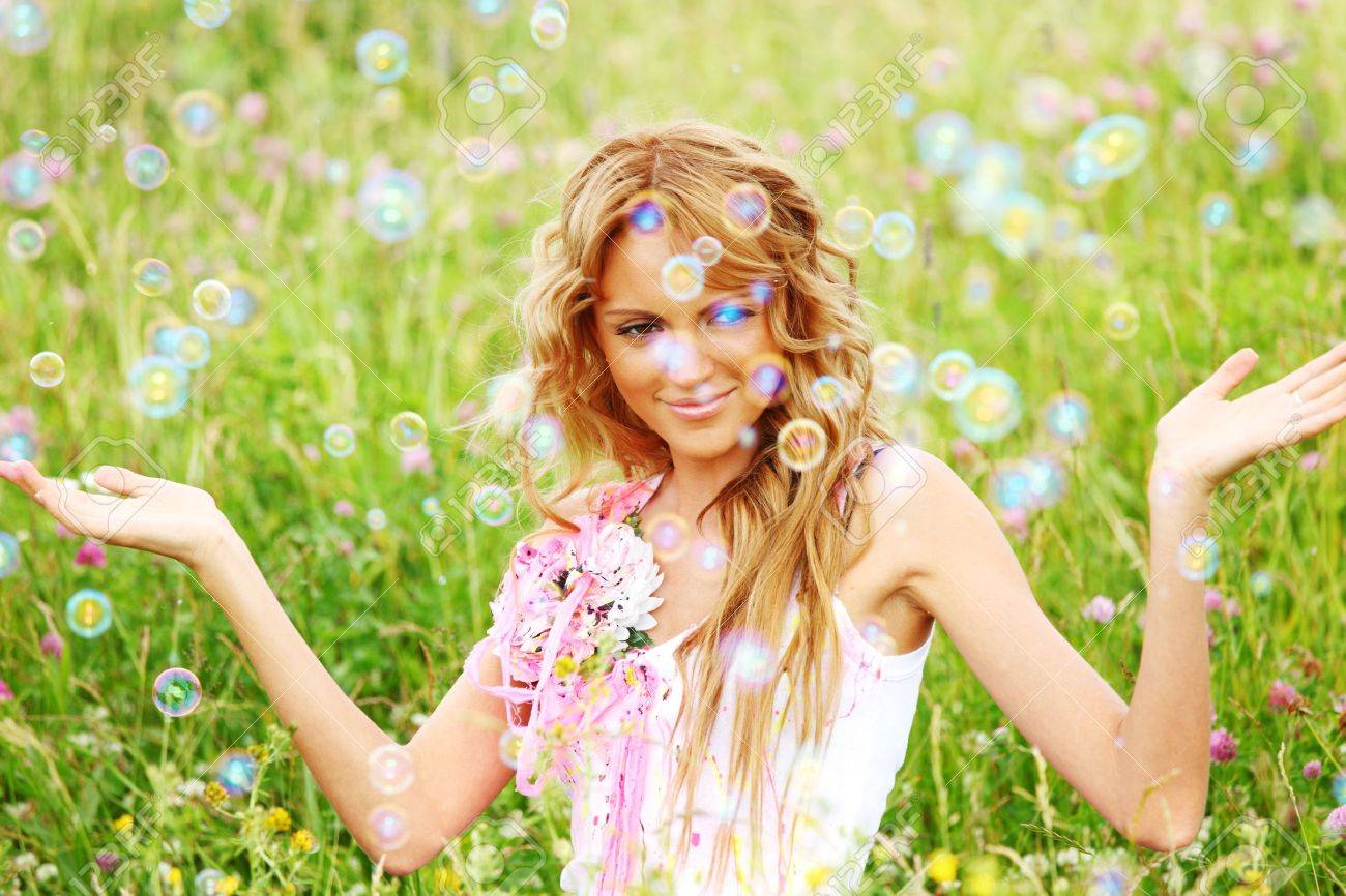 Blonde starts soap bubbles in a green field Stock Photo - 8752763