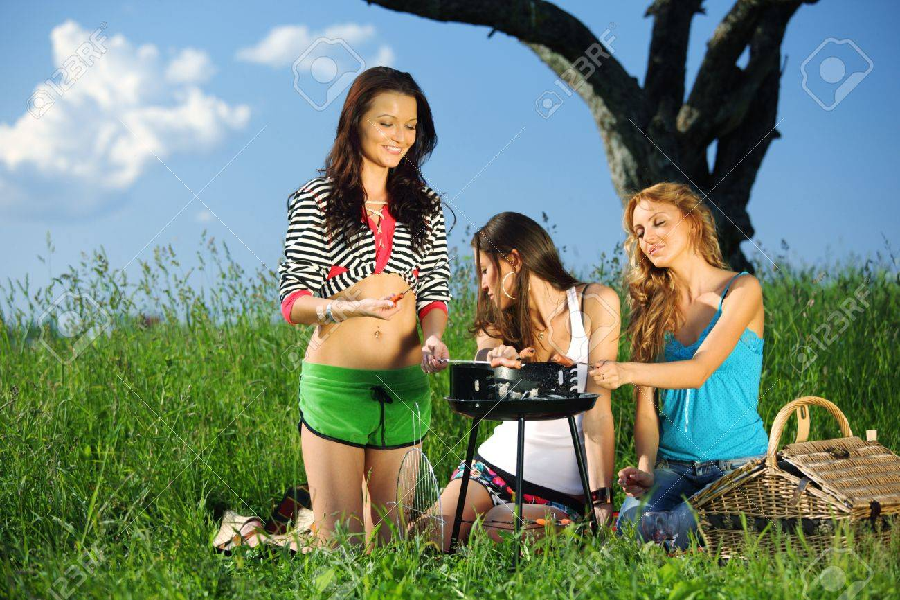 girls burn sausages on barbecue Stock Photo - 8826145