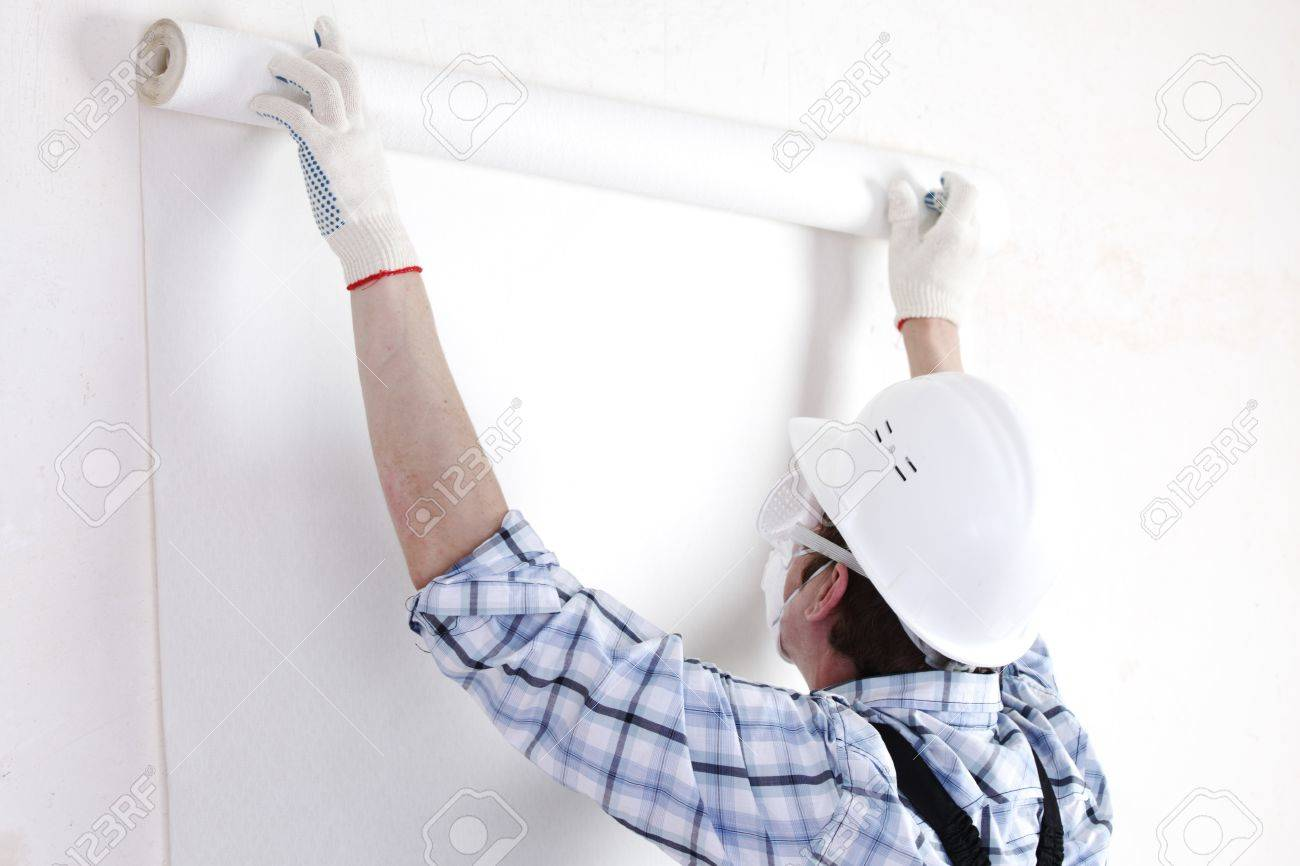worker attaching wallpaper to wall Stock Photo - 9006798