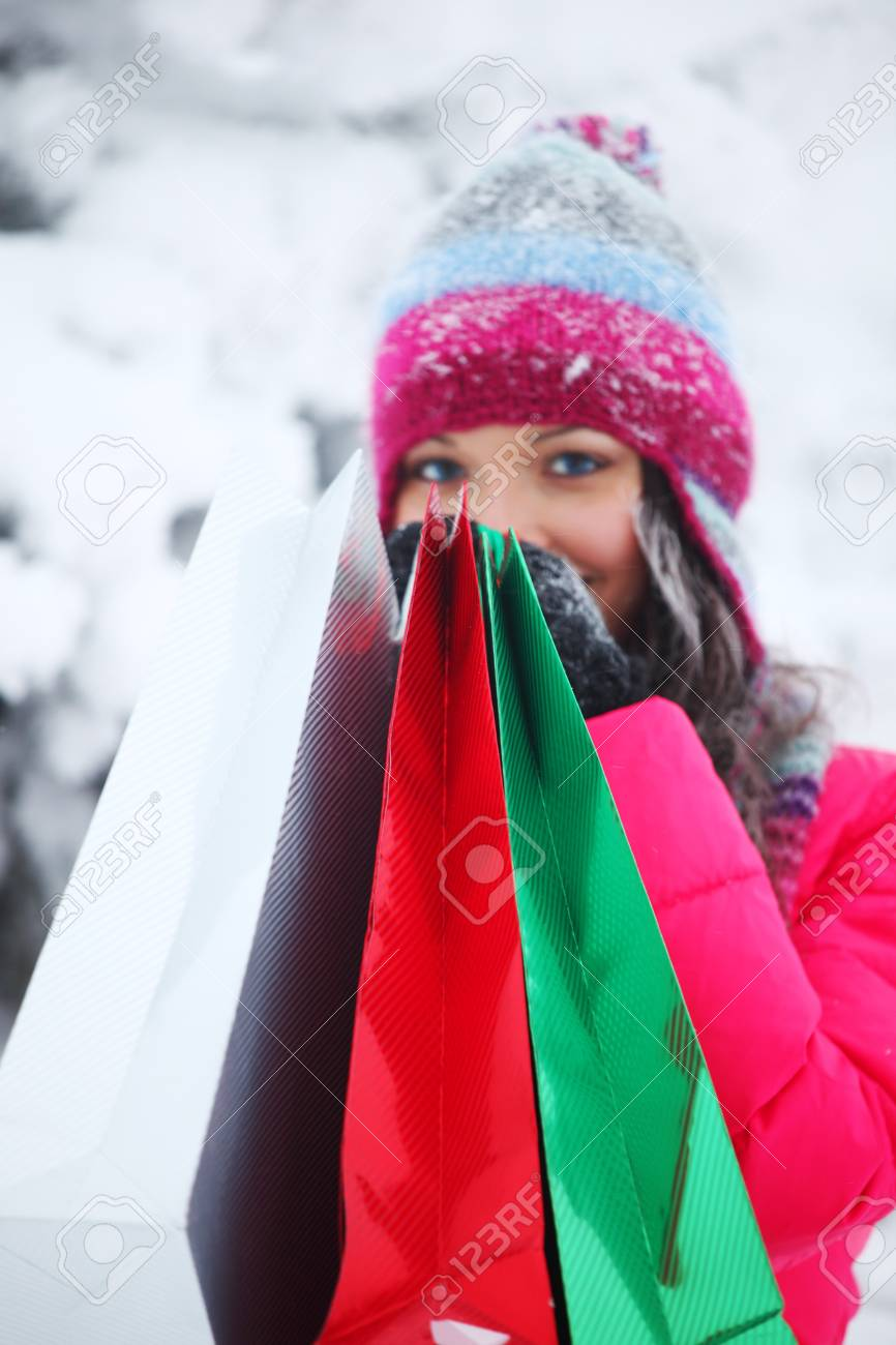 winter girl with gift bags on snow background Stock Photo - 9173655