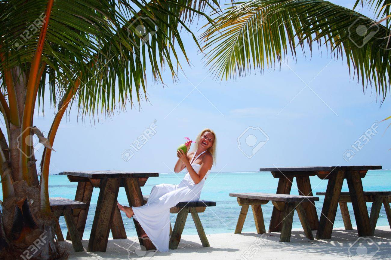 woman sitting in a tropical cafe on the background of a  palm trees and sky and sea Stock Photo - 10895911