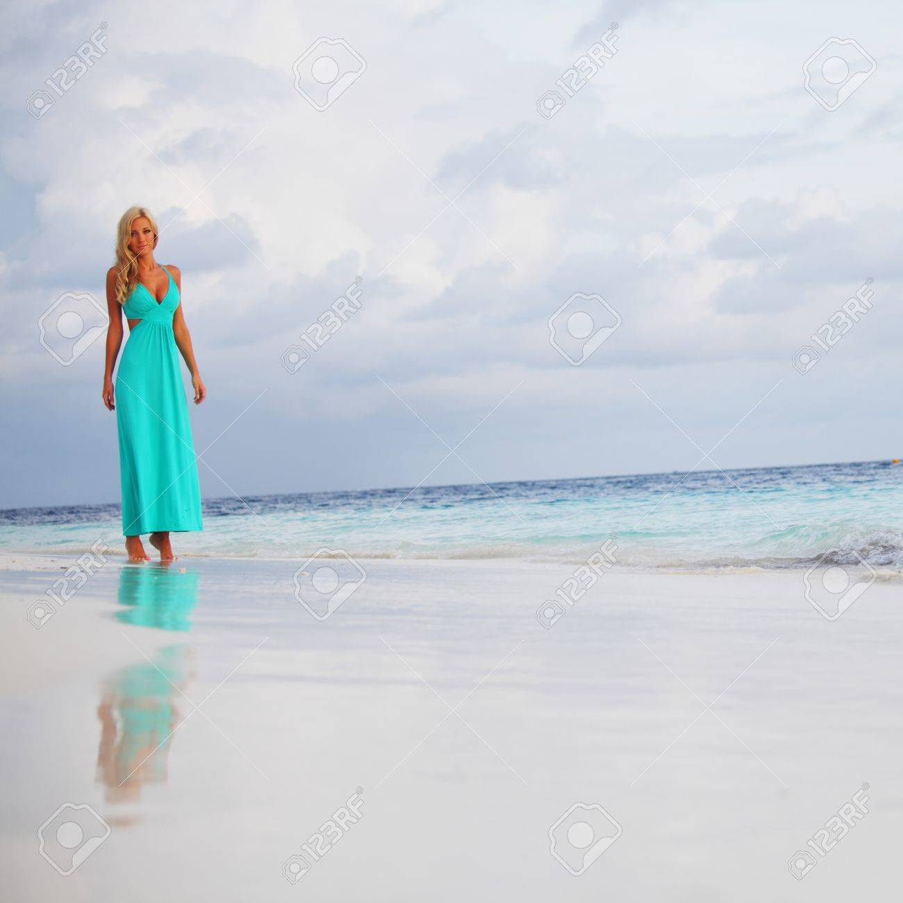 woman in a blue dress on the ocean coast Stock Photo - 10895813