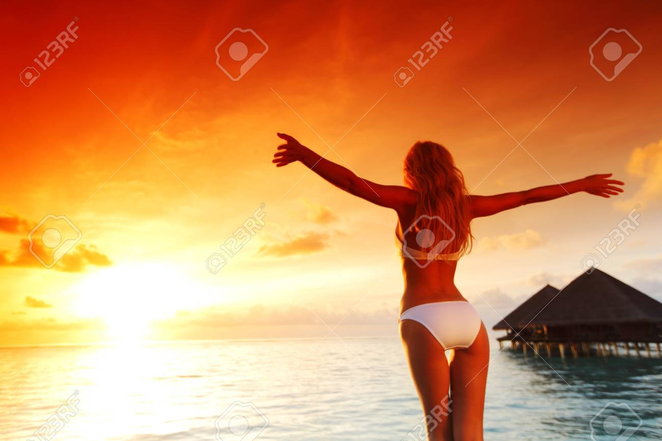 woman in a dress on a bridge home sea and the maldivian sunset on the background Stock Photo - 10895880