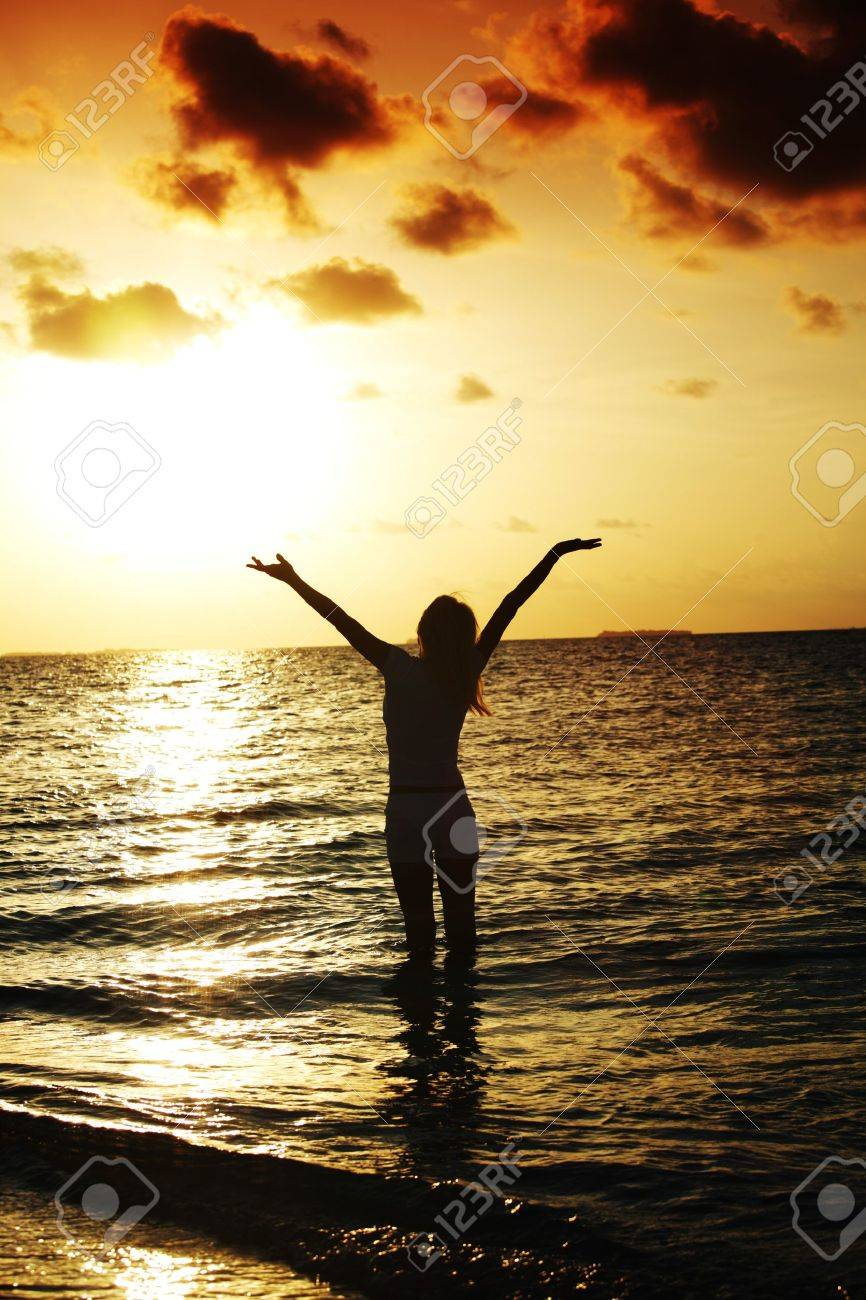 happy woman standing on a sunset in ocean waves Stock Photo - 11367981