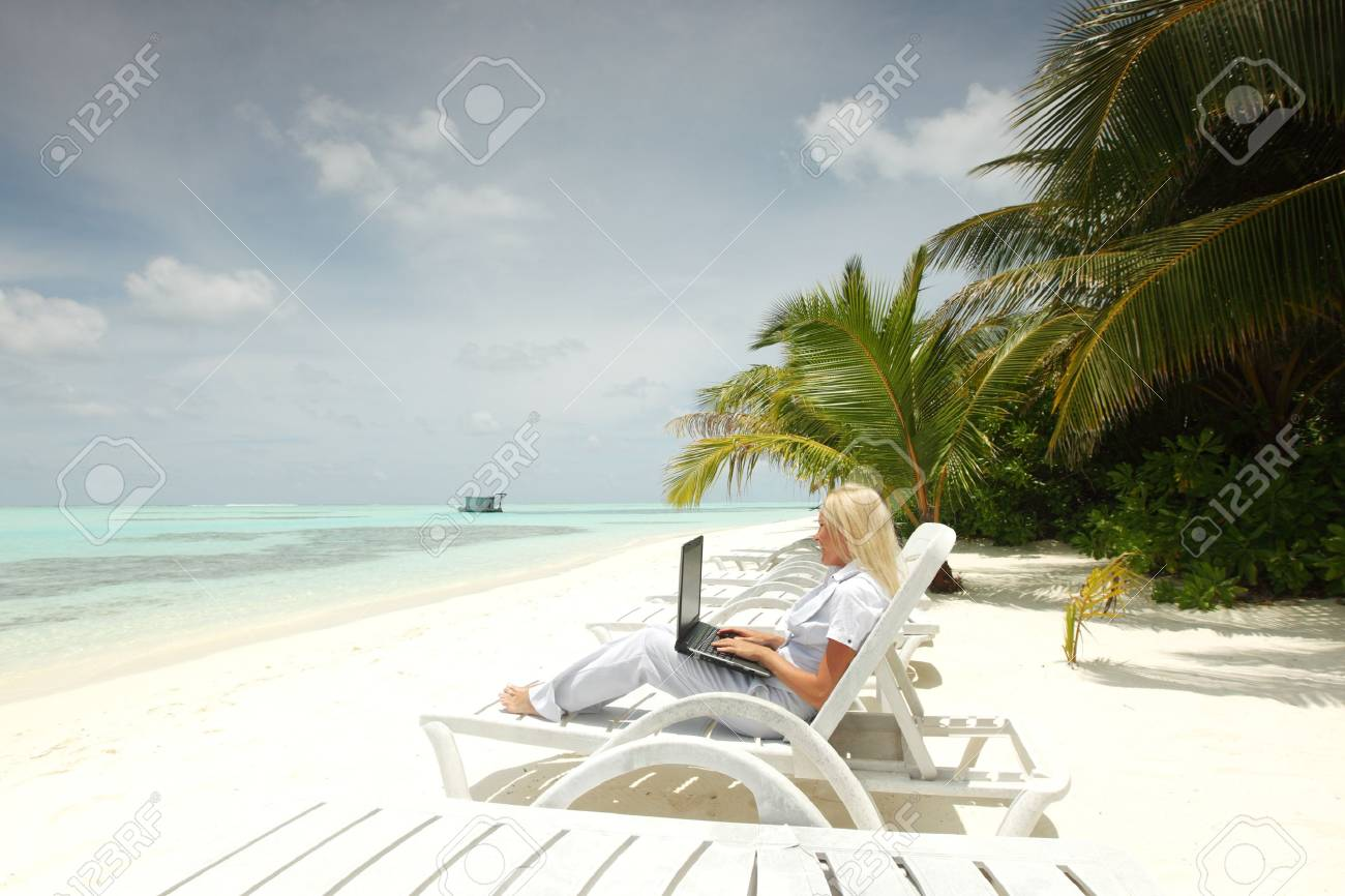 business woman with laptop lying on a chaise lounge in the tropical ocean coast Stock Photo - 11408677